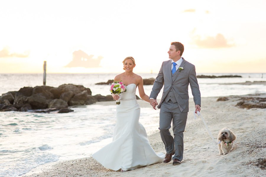 bride and groom walk at fort zachary beach with their doggie