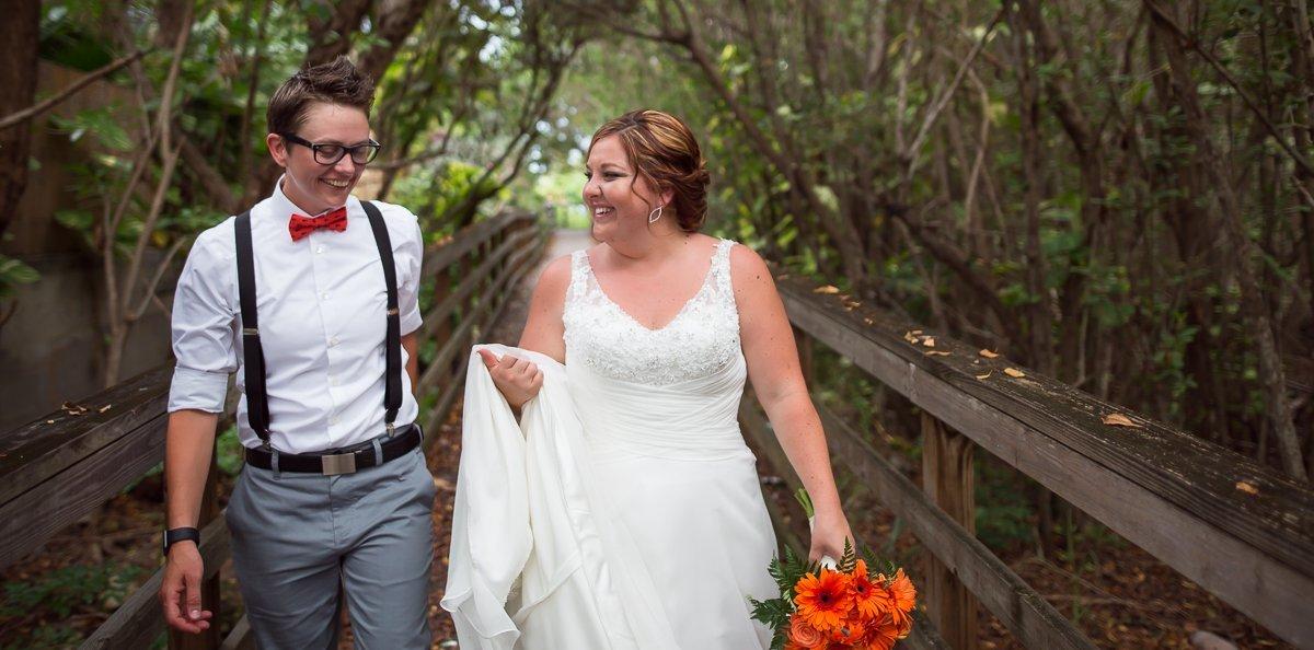 same sex couple takes a stroll on a boardwalk in key west