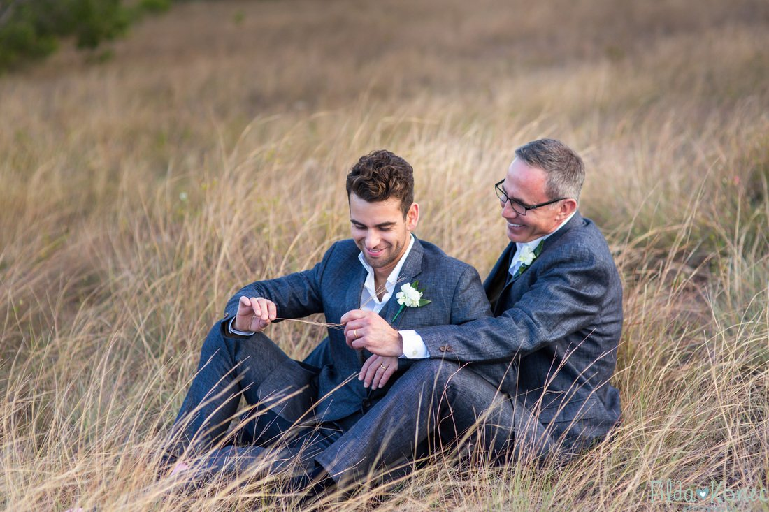 gay couple sitting in the grass in key west florida