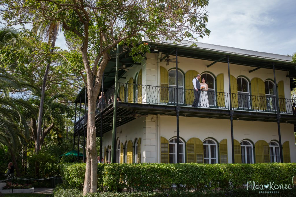 bride and groom on the balcony at hemingway home in key west florida