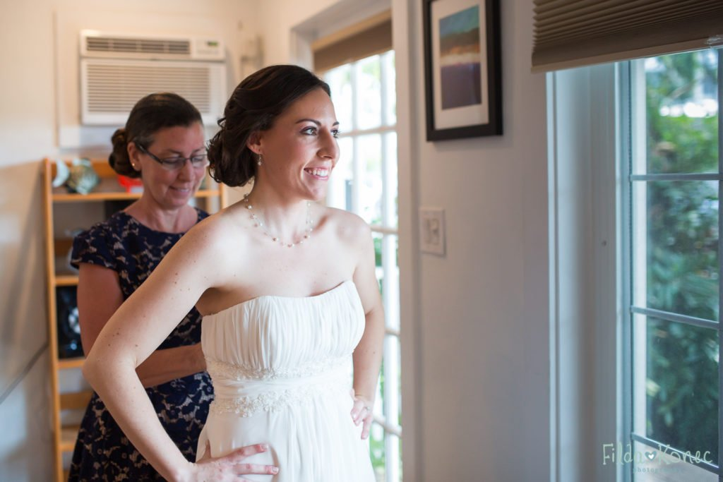 bride's mom helping her to finish up getting in to her wedding dress