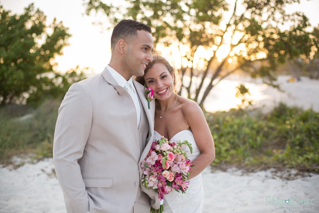 bride and groom on the beach with sunset