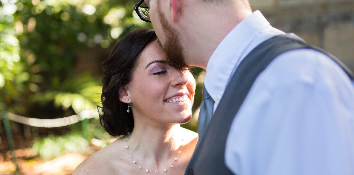 groom kisses his bride before their hemingway home wedding in key west