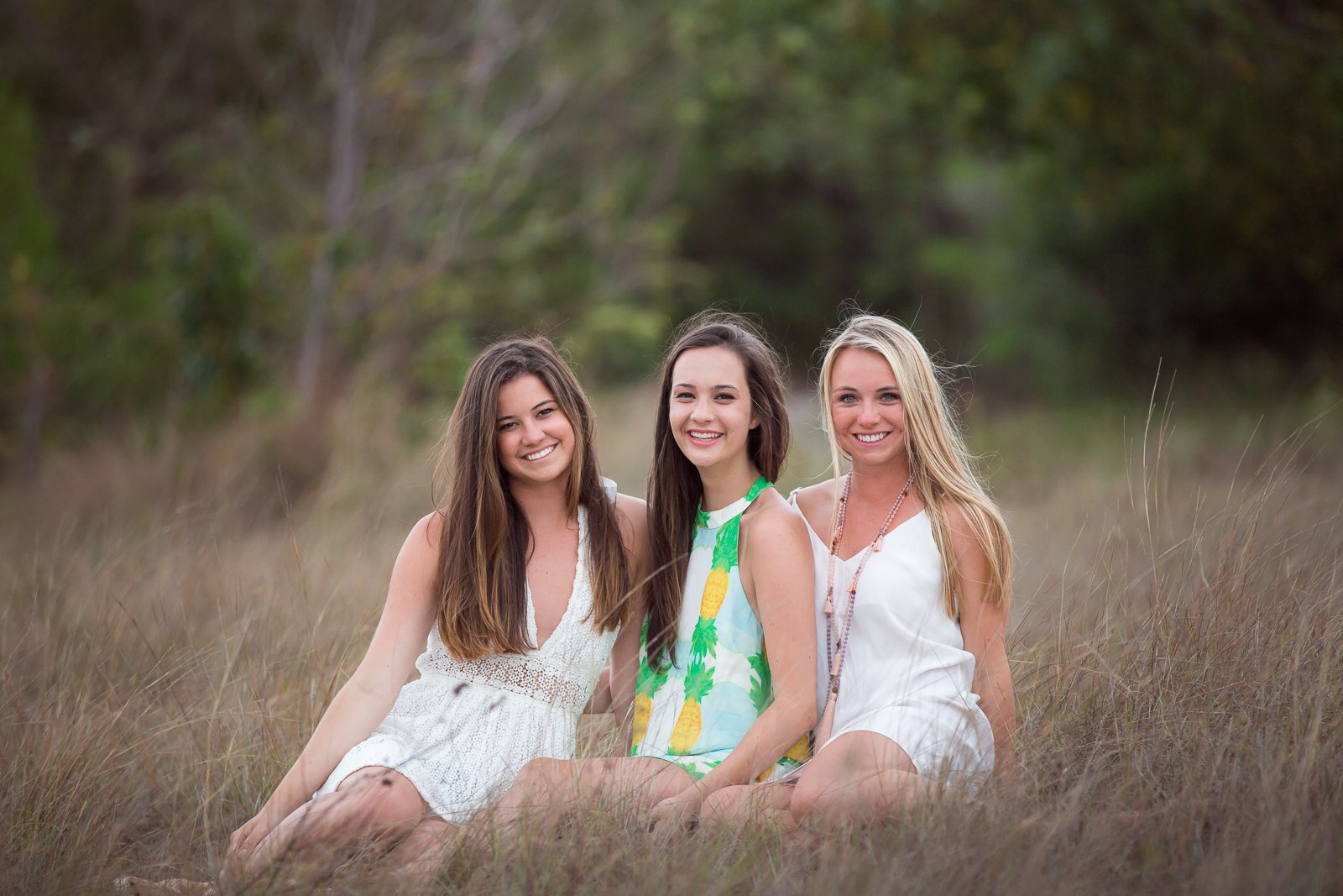 3 girls sitting in the grass posing for family photo