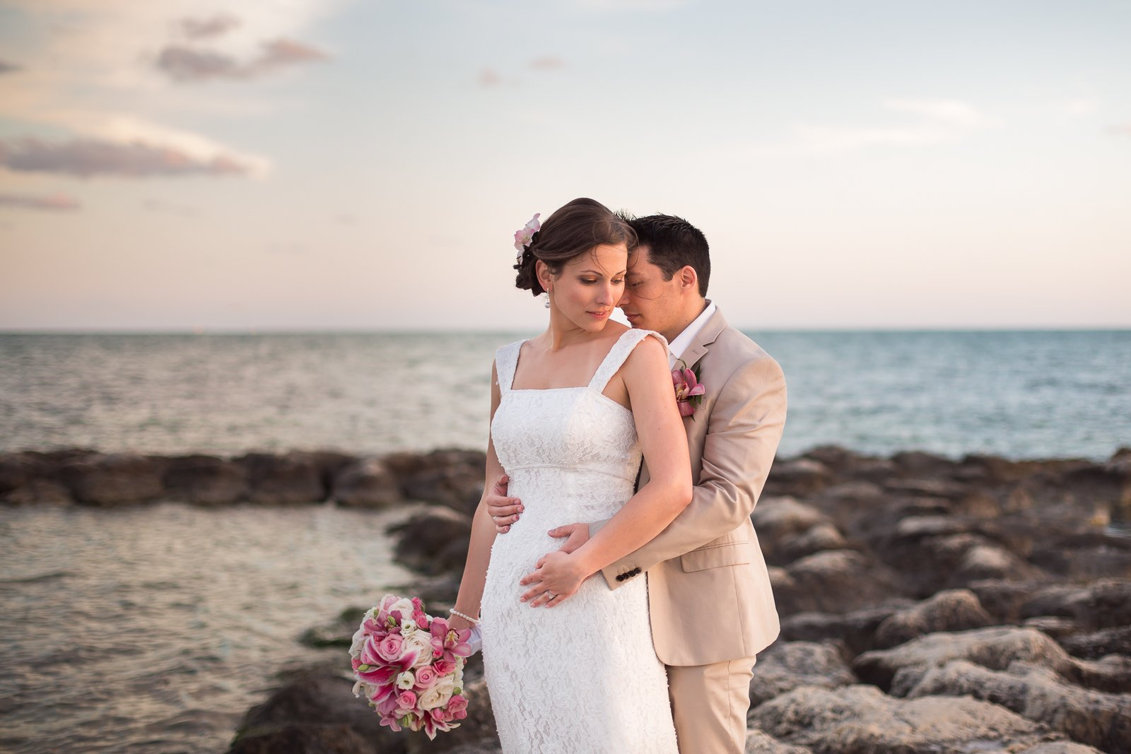 bride and groom posing on rock on the beach in key west, fl