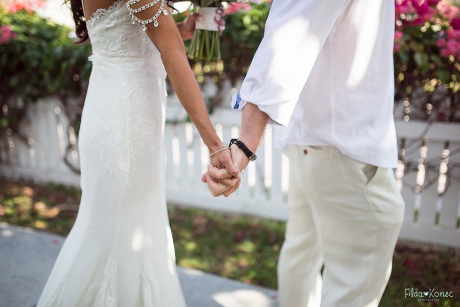 bride and groom touch their hands before their beach wedding