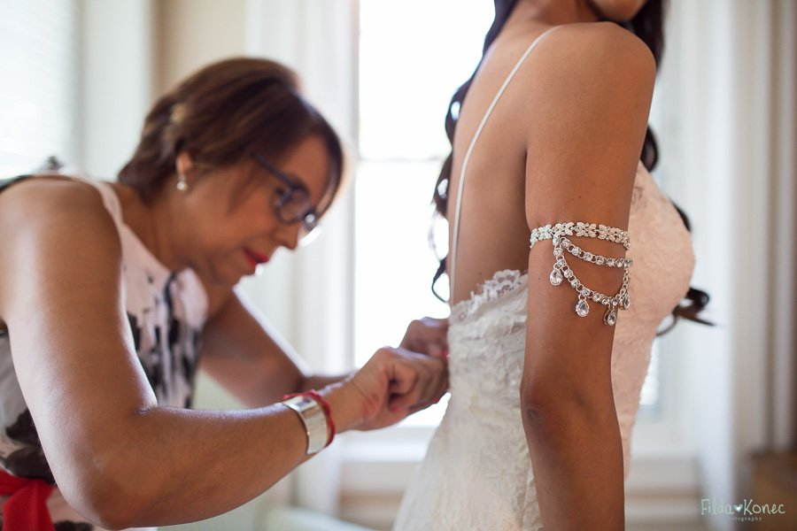 mother of the bride helping her to get in to the wedding dress