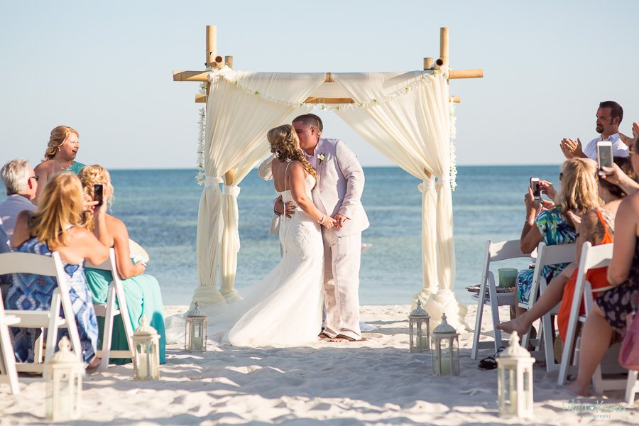 bride and groom first kiss at beach altar