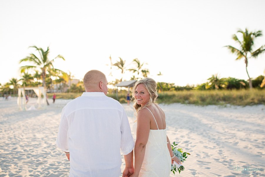 bride looks at camera walking with groom on the beach in key west florida