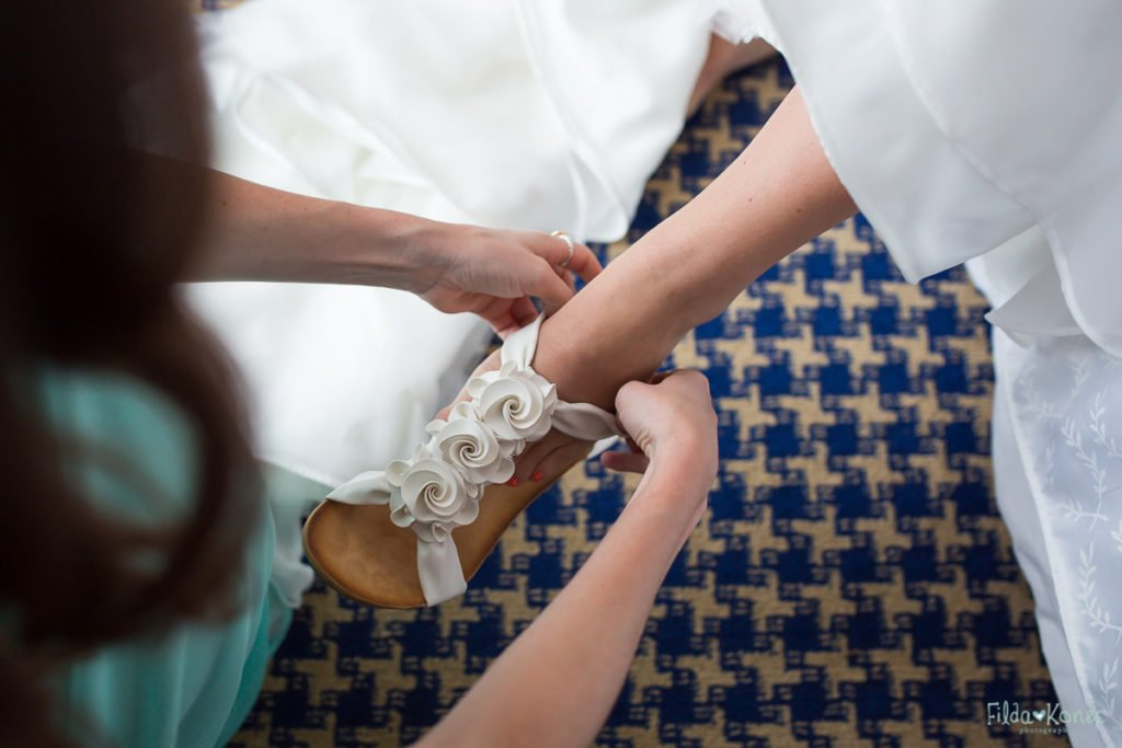 bride is putting her wedding shoes on