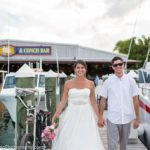 bride and groom walk on the pier