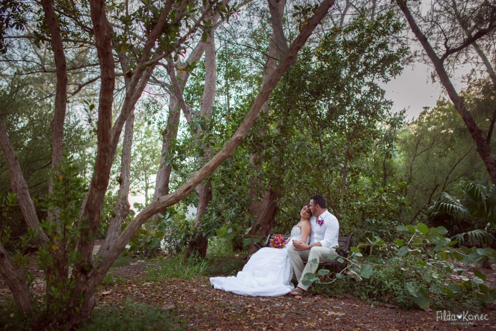bride and groom sit on the bench in key west nature