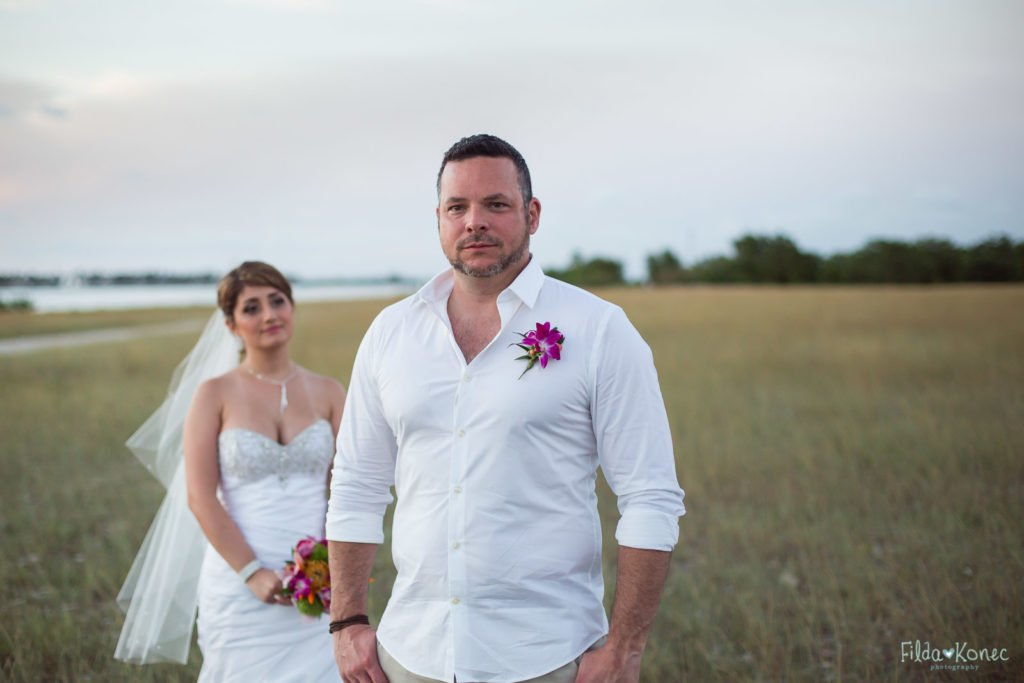 portrait of groom with bride in the background
