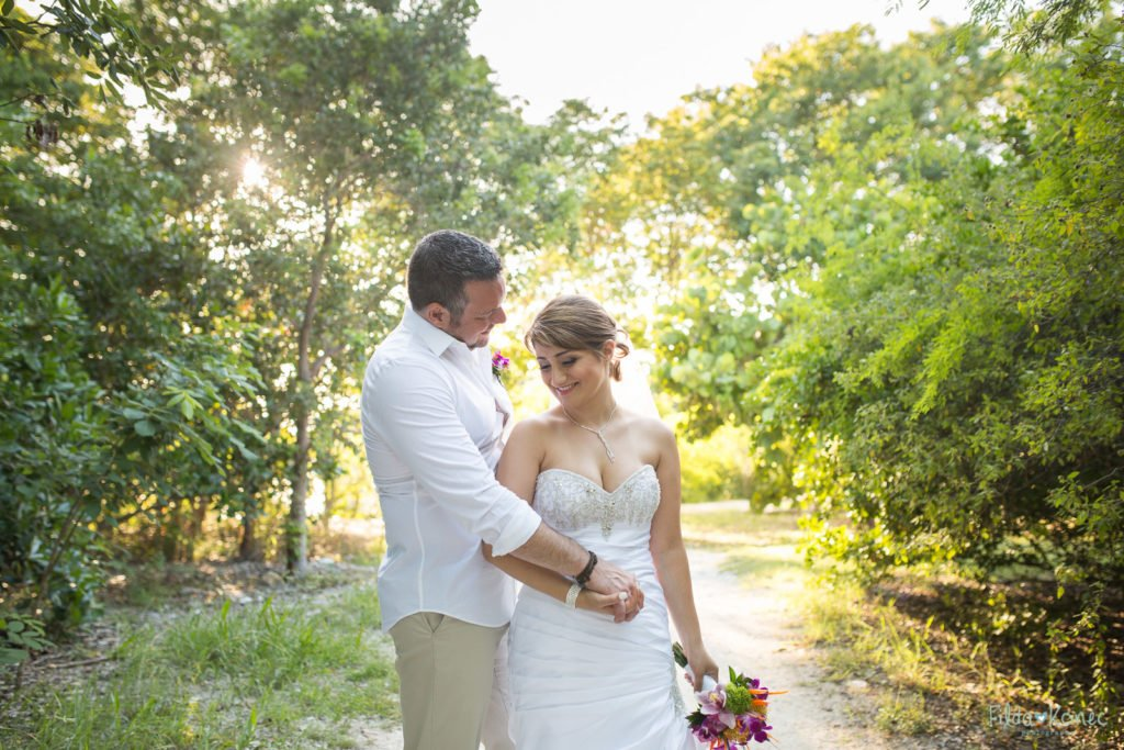 groom holding his bride at beautiful park