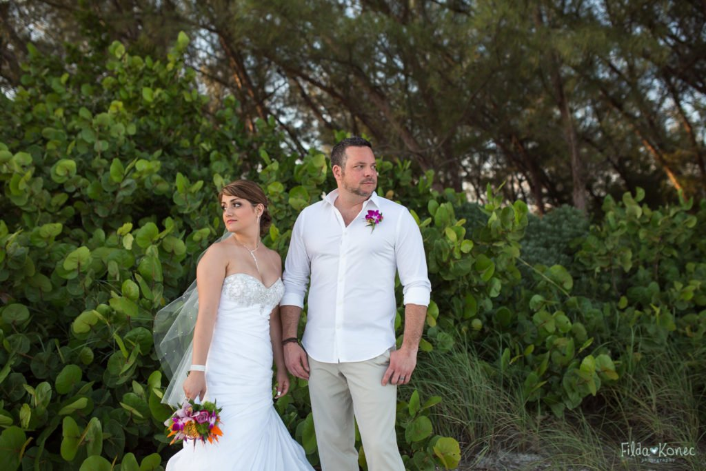 bride and groom looking away with green foliage in the background