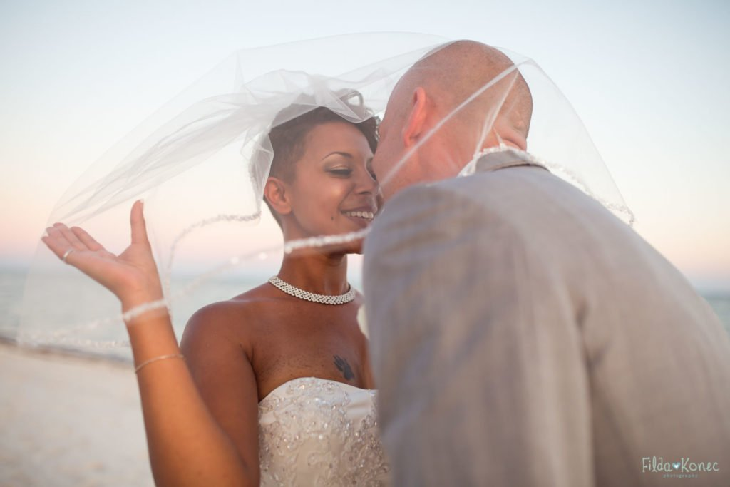 Bride and groom kiss under the veil on Smather's beach in Key West, FL