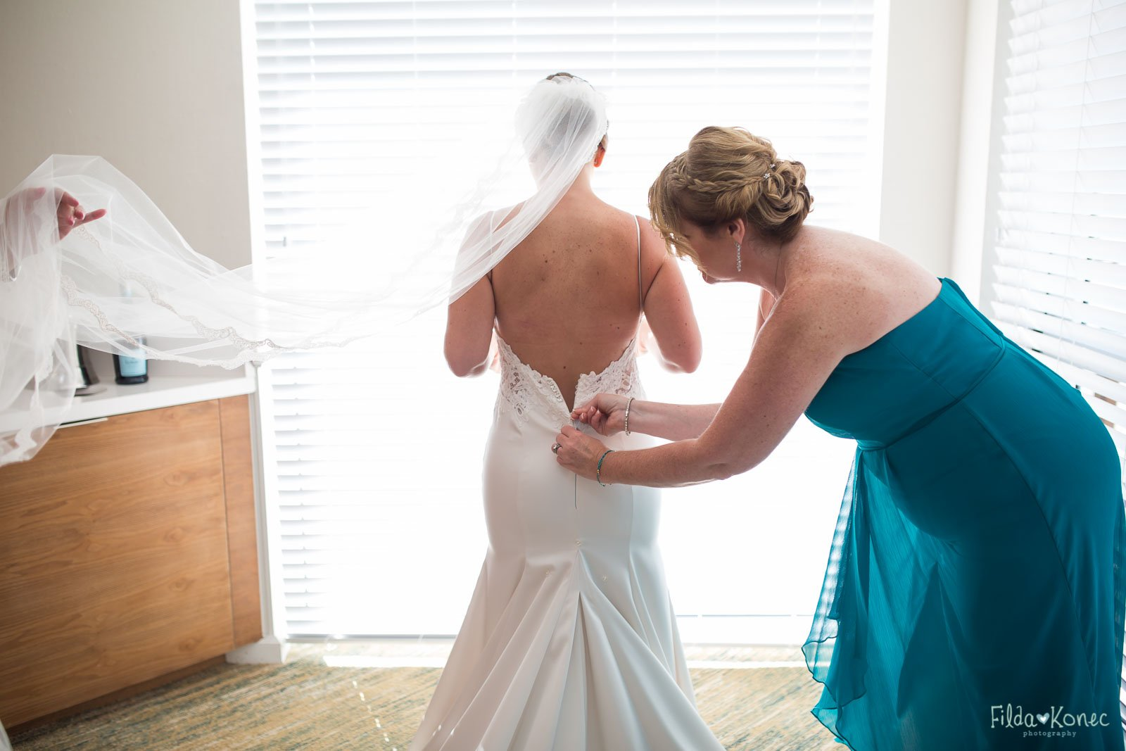 bride is getting into her dress for her key west wedding