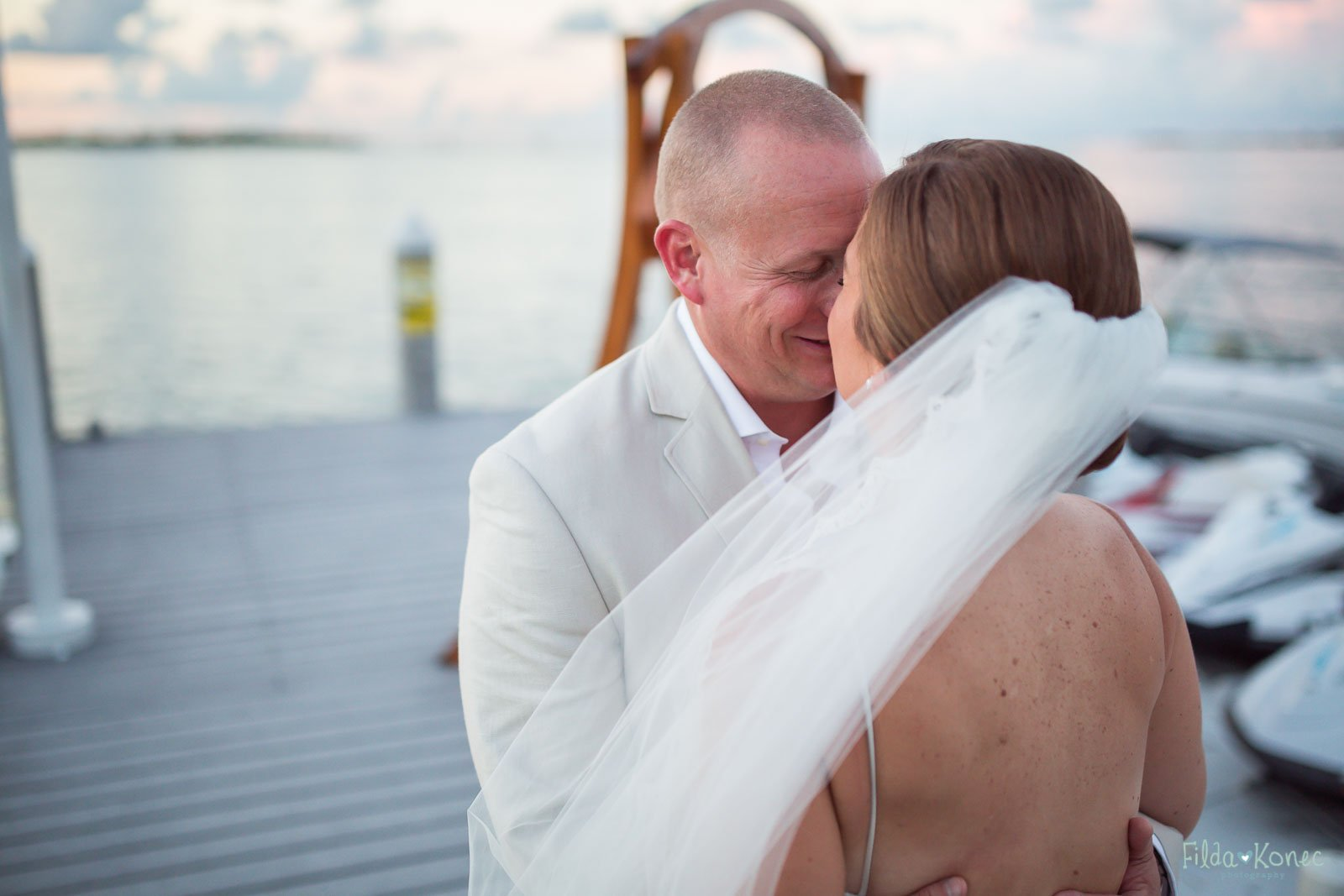 bride and groom snugly looking at each other near atlantic ocean in key west