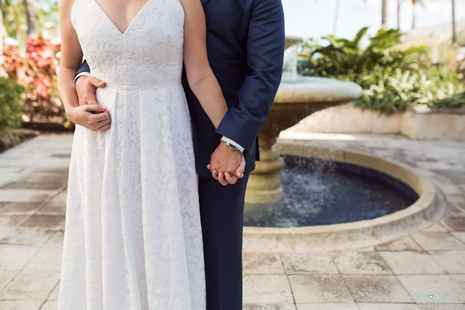 close up of grooms hands holding bride