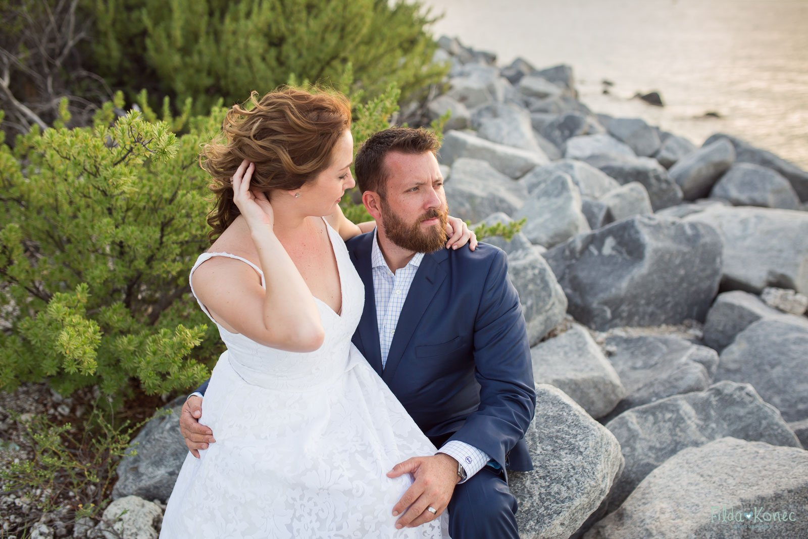 bride and groom on the rocks by the ocean