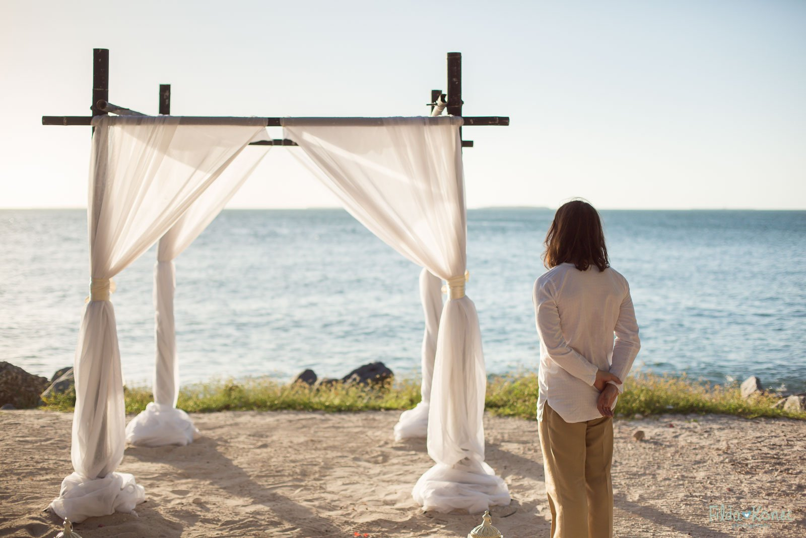 groom awaits his bride for their beach ceremony at fort zachary taylor beach in key west florida
