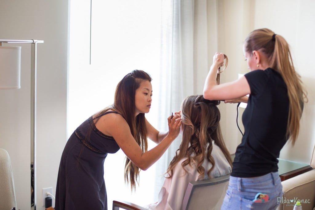 hair and makeup artists working on bride