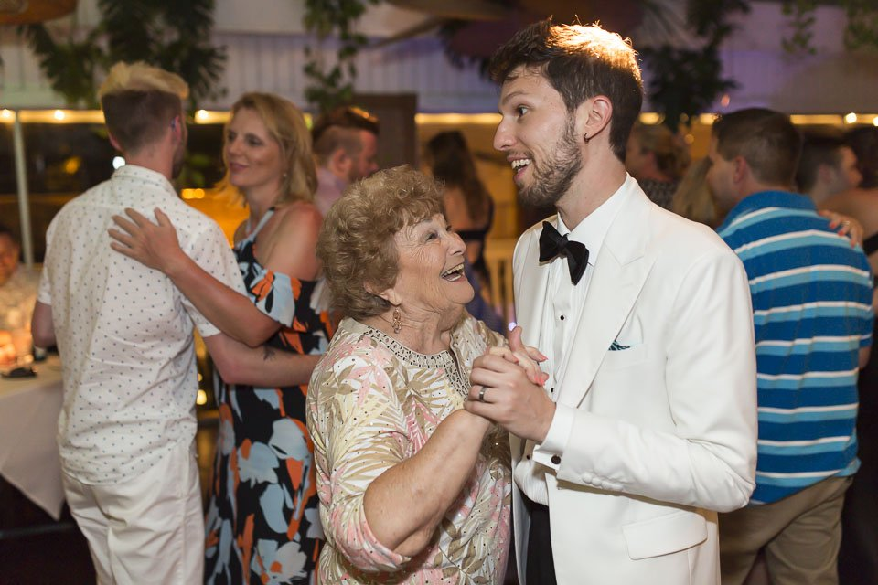 groom dances with his grandma at roof top cafe reception