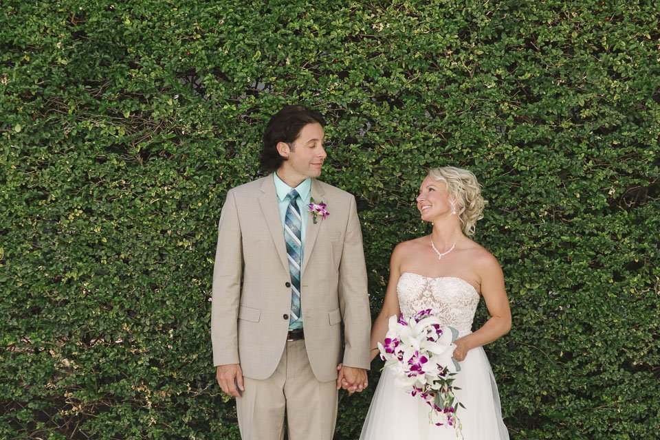 bride and groom in front of hedge in key west florida
