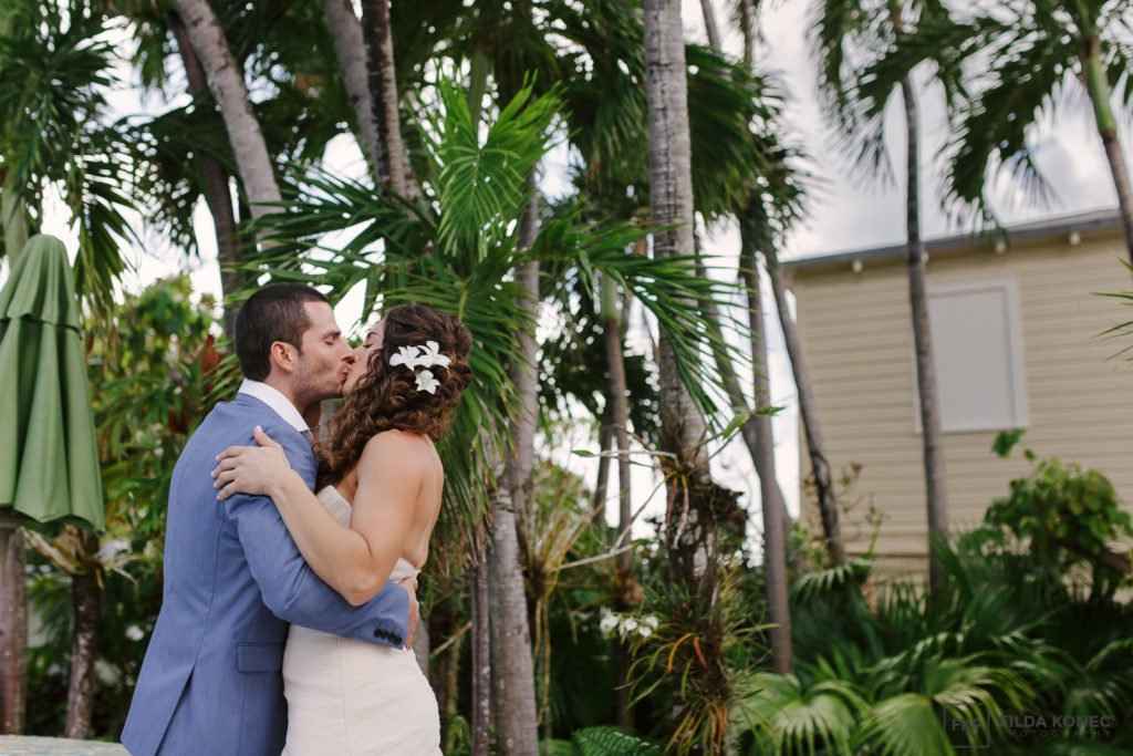 bride and groom kiss in key west garden