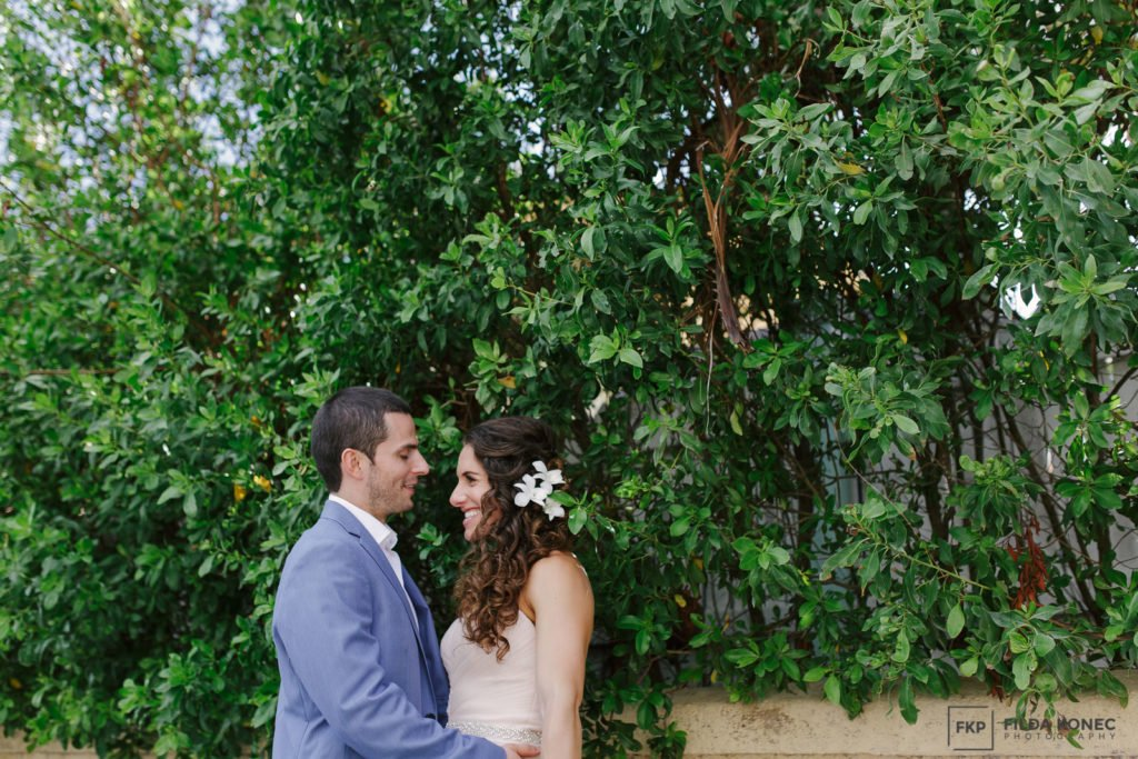 beautiful couple laughs with green hedges in the background