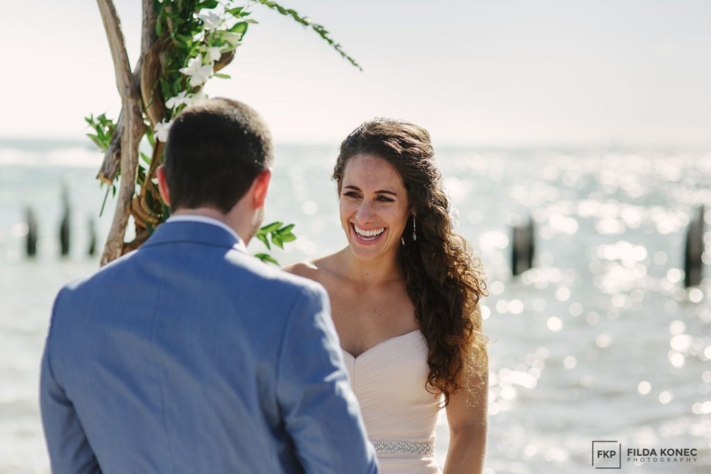 bride laughs during beach ceremony