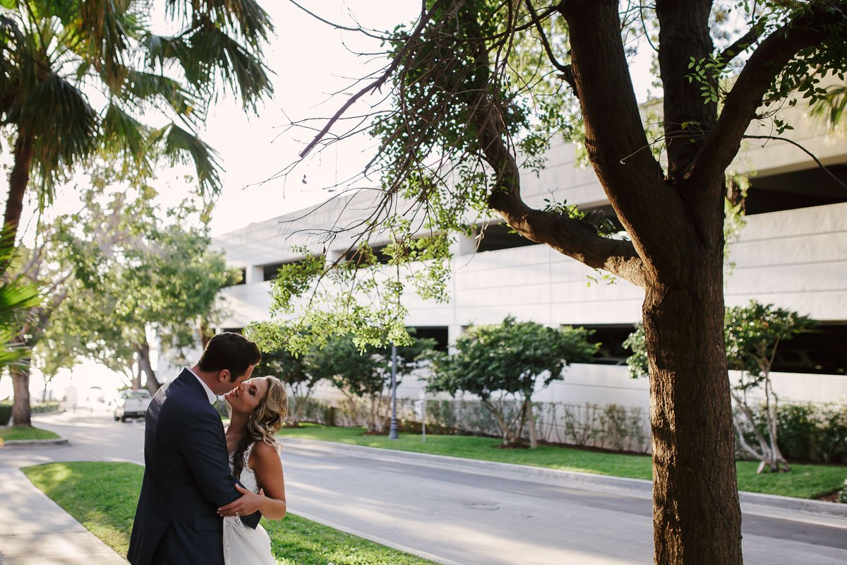 bride and groom kiss by parking garage in key west