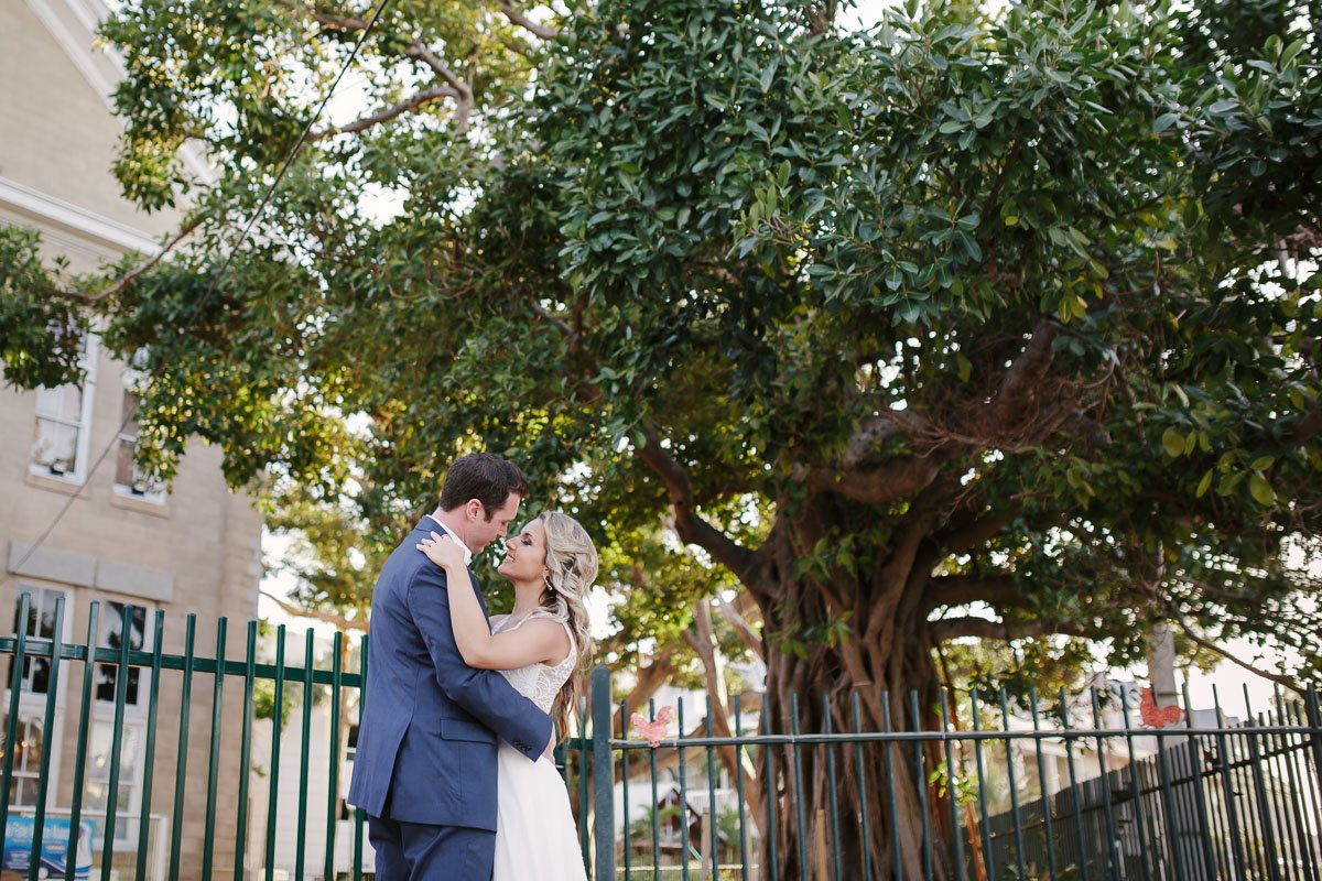 bride and groom hug near a key west tree