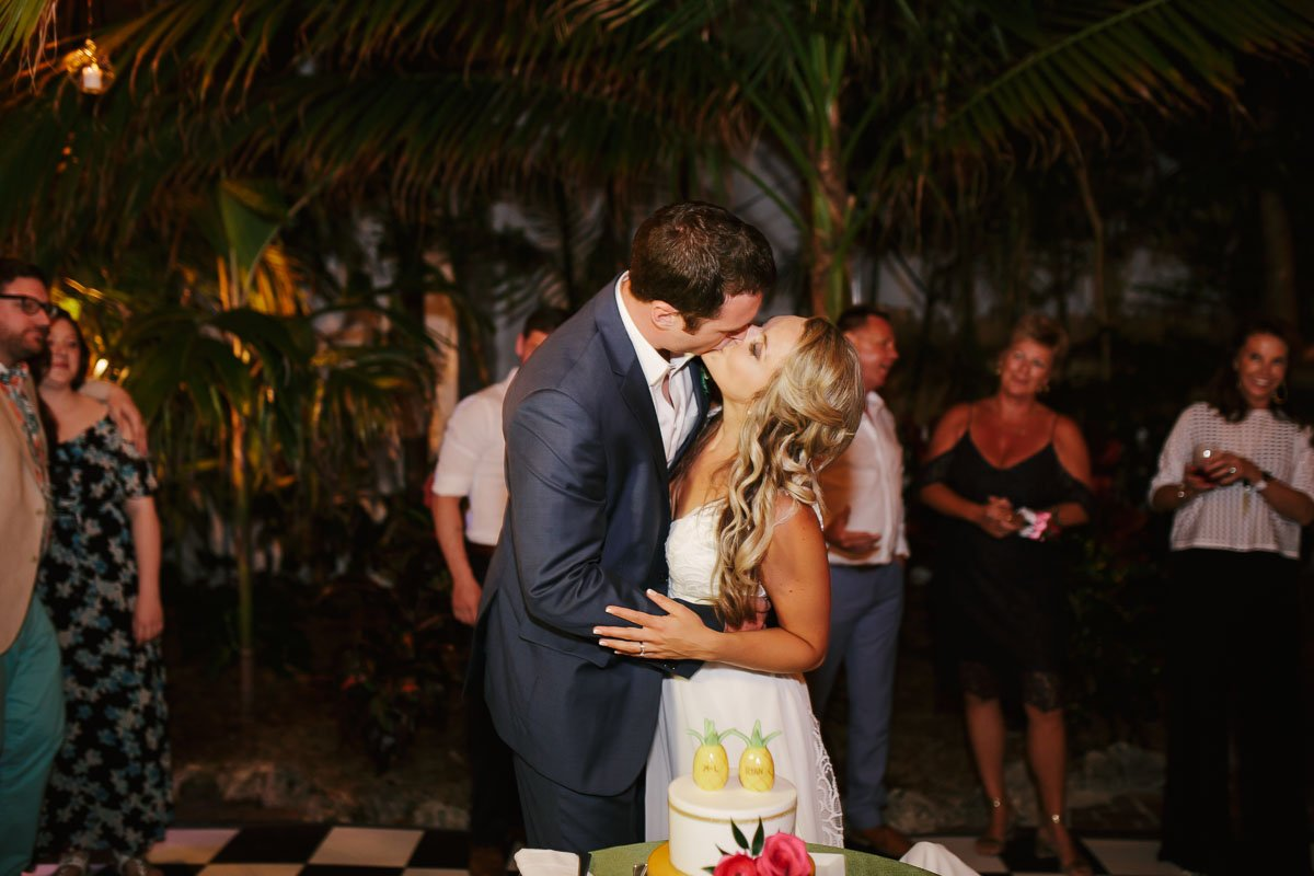 groom and bride kiss with wedding cake in key west