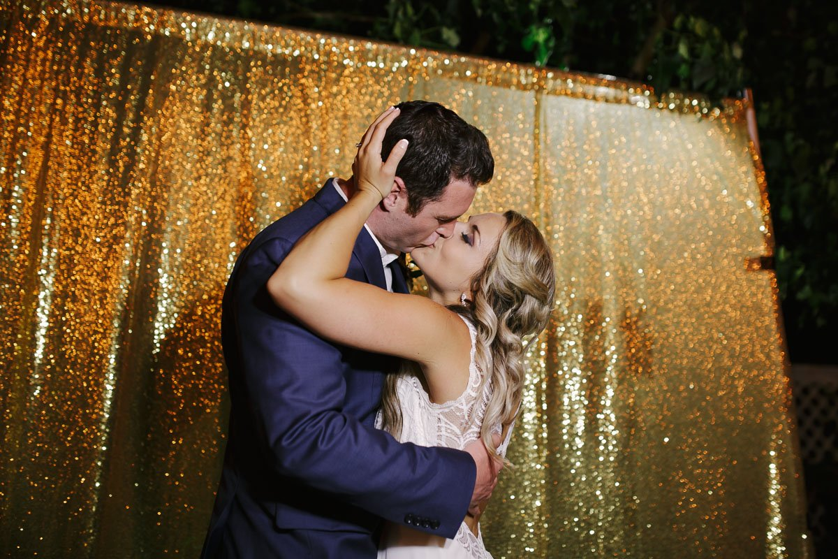 bride and groom kiss at the photobooth